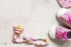 Rosa byten, nippel och rosa pläd på en grå bakgrund Det begreppet av att förvänta behandla som ett barn flickan, havandeskap dott arkivfoto