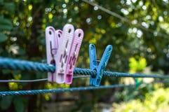 Rosa colorido e azul do pregador de roupa dois na corda foto de stock
