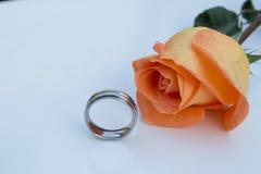 Rosa cromada y anaranjada del anillo de bodas, en el fondo blanco fotos de archivo
