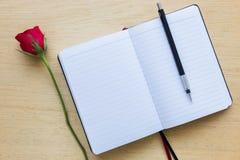 Rosa, cuaderno y lápiz del rojo en el fondo de madera imagen de archivo libre de regalías