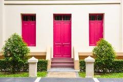 rosa dörr, rosa fönster på den kräm- väggen på rosa trappuppgång med sma Royaltyfri Bild