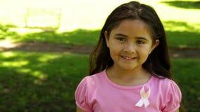 Rosa d'uso sorridente della bambina per consapevolezza del cancro al seno nel parco archivi video