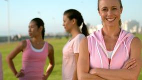 Rosa d'uso sorridente della donna per cancro al seno davanti agli amici stock footage