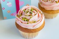 A rosa de dois pêssegos rodou bolos geados do copo com o spri da porca de pistache Fotos de Stock Royalty Free