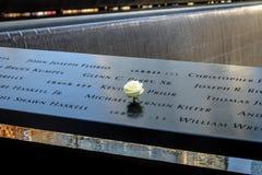 Rosa del blanco del cumpleaños cerca del nombre de la víctima grabada en el parapeto de bronce de 9/11 monumento en el World Trad Fotos de archivo libres de regalías