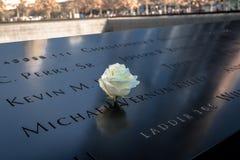 Rosa del blanco del cumpleaños cerca del nombre de la víctima grabada en el parapeto de bronce de 9/11 monumento en el World Trad Imagen de archivo libre de regalías