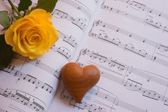 Rosa del corazón y del amarillo en una hoja de la música Foto de archivo