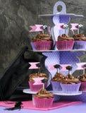 Rosa del día de graduación y magdalenas púrpuras del chocolate del partido en soporte Imagen de archivo