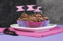 Rosa del día de graduación y magdalenas púrpuras del partido en la placa Imagen de archivo libre de regalías