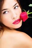 Rosa del rojo cerca de los labios y del hombro descubierto Imágenes de archivo libres de regalías