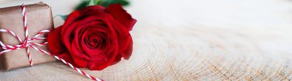 Rosa del rojo con el regalo en la madera rústica brillante Foto de archivo libre de regalías