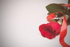 Rosa del rojo con la cinta en un fondo de madera ligero Día de Women s, Fotografía de archivo libre de regalías