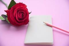 Rosa del rojo, cuaderno, lápiz rosado en fondo rosado Foto de archivo