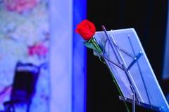 Rosa del rojo en soporte de las notas de la música imagen de archivo libre de regalías