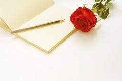 Rosa del rojo en un cuaderno y un lápiz en estilo del vintage Foto de archivo libre de regalías