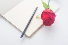 Rosa del rojo en un cuaderno y un lápiz en estilo del vintage Fotografía de archivo libre de regalías