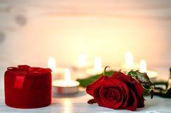 Rosa del rojo que miente en blanco una superficie de madera En el fondo se encienden las pequeñas velas Imagen de archivo libre de regalías