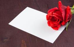 Rosa del rojo y carte cadeaux en blanco para el texto en viejo fondo de madera Imagen de archivo