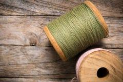 Rosa della bobina con la destra verde del filato su legno Fotografia Stock