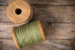 Rosa della bobina con la parte di sinistra del filato verde su legno Fotografia Stock