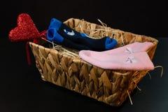 Rosa di bambino e calzini blu e bugia del cuore in un canestro sul fieno, su un fondo nero immagini stock libere da diritti