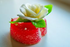 Rosa di bianco con le foglie verdi su un cuore rosso della marmellata d'arance, i dolci per gli amanti e le nozze Fotografia Stock