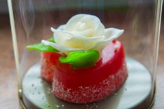 Rosa di bianco con le foglie verdi su un cuore rosso della marmellata d'arance, i dolci per gli amanti e le nozze Immagine Stock Libera da Diritti