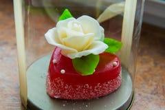 Rosa di bianco con le foglie verdi su un cuore rosso della marmellata d'arance, i dolci per gli amanti e le nozze Immagini Stock Libere da Diritti