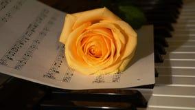 Rosa di giallo sulle note e sul piano Fotografie Stock Libere da Diritti