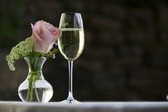Rosa di rosa con un vetro di vino bianco. Immagini Stock