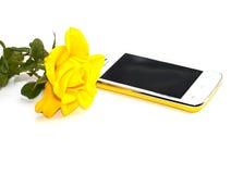 A rosa do amarelo e amarela brilhantemente o telefone, ainda vida Foto de Stock