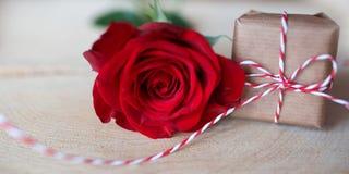 Rosa do vermelho com o presente na madeira rústica brilhante Fotografia de Stock Royalty Free