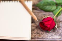 Rosa do vermelho em assoalhos de madeira velhos e um caderno e uma pena Imagens de Stock