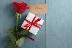 Rosa do vermelho na tabela de madeira azul com o cartão de papel do dia da caixa de presente e do 8 de março Foto de Stock Royalty Free