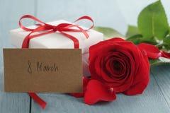 Rosa do vermelho na tabela de madeira azul com o cartão de papel do presente e do 8 de março Fotos de Stock