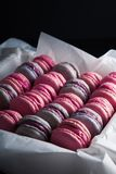 Rosa dolce, biscotti francesi viola del maccherone in una scatola su fondo nero fotografia stock libera da diritti