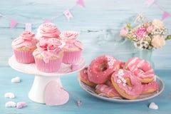 Rosa donuts och koppkakor royaltyfri fotografi