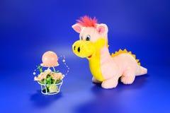 Rosa Drachespielzeug mit dekorativer Kerze mit Blumen Stockfotos