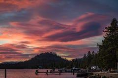 Rosa dramático y puesta del sol azul con una colina, un barco y un doc. redondos de la playa de la orilla del lago en el lago Tah imágenes de archivo libres de regalías