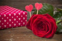 Rosa e caixa de presente do vermelho em uma tabela de madeira velha Fotografia de Stock