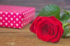 Rosa e caixa de presente do vermelho em uma tabela de madeira velha Imagens de Stock Royalty Free