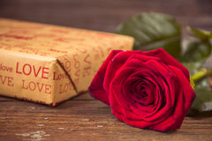 Rosa e caixa de presente do vermelho em uma tabela de madeira velha Foto de Stock