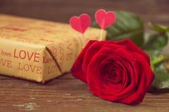 Rosa e caixa de presente do vermelho em uma tabela de madeira velha Imagens de Stock