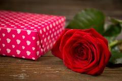 Rosa e caixa de presente do vermelho em uma tabela de madeira velha Fotografia de Stock Royalty Free