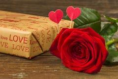 Rosa e caixa de presente do vermelho em uma tabela de madeira velha Fotos de Stock Royalty Free