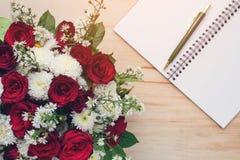 Rosa e livro vazio com a pena na tabela de madeira Fotos de Stock Royalty Free