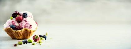 Rosa Eiscreme mit Beeren, Erdbeeren, Blaubeeren, Himbeeren, Pistazien im Waffelkorb Sommerlebensmittelkonzept lizenzfreies stockbild