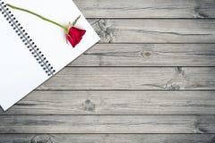 Rosa em um livro na tabela de madeira Fotografia de Stock Royalty Free