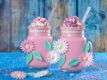 Rosa enhörningmilkshake med piskade kräm, socker och stänk royaltyfria foton