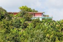 Rosa färg- och gräsplanstuckaturhem på den tropiska kullen Arkivfoto